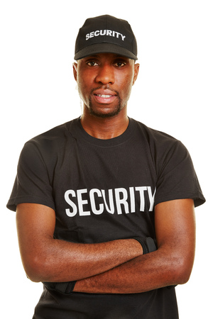 job security: Smiling black man as security guard with his arms crossed