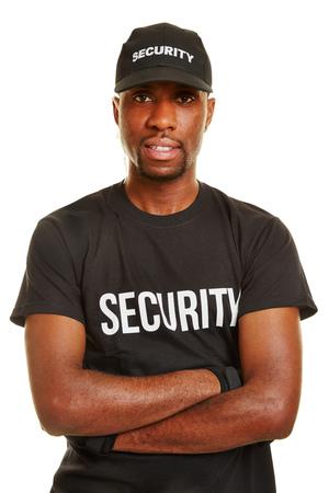 seguridad en el trabajo: Sonriente hombre de negro como guardia de seguridad con los brazos cruzados