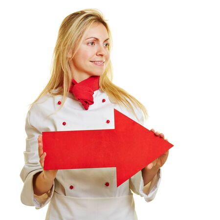 workwear: Young female cook in workwear holding a big red arrow Stock Photo