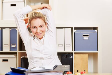 Smiling young business woman stretching in her office