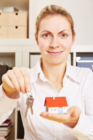 key handover: Female realtor with a small house and keys on a keychain in her hands