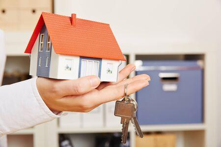 Main d'une femme tenant une petite maison avec deux clés