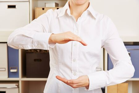invisible object: Empty hands of a business woman in office holding invisible object