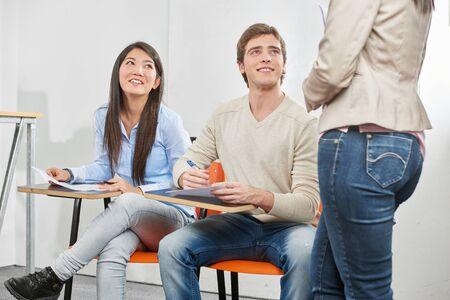 Adolescente et un garçon tenant un test dans leur salle de classe de l'école secondaire