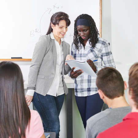 african student: Teacher helps her african student with ther presentation