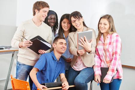 Nauczyciel i uczniowie z uśmiechem swojego tabletu w klasie