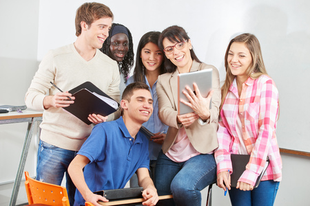 Teacher and students smiling with their tablet in class Stock Photo