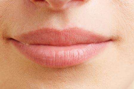 Close-up van gesloten vrouwelijke mond met volle lippen