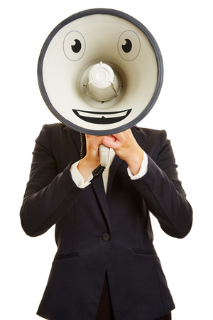 speaking tube: Smiley face on a megaphone in front of a businesswoman Stock Photo