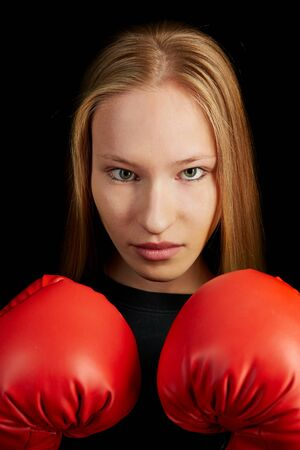 young beautiful woman: Young woman learning self-defense with red boxing gloves Stock Photo