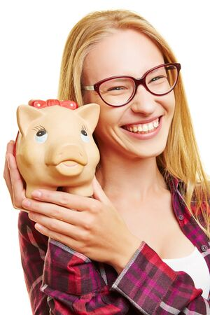 thrift box: Smiling young woman holding piggy bank in her hands Stock Photo