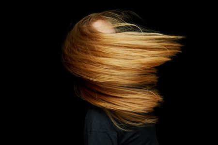 Blonde woman dancing with long flying hair at night