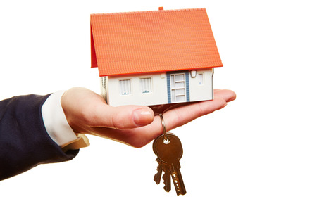 Weibliche Hand ein kleines Haus mit Tasten gedrückt halten