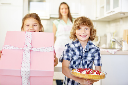 child birthday: Two children with gift and fruit cake for a birthday in the kitchen Stock Photo