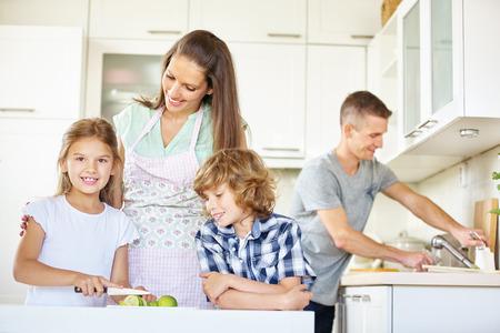niños desayunando: Familia con dos hijos que trabaja en cocina y corte de frutos de limón Foto de archivo