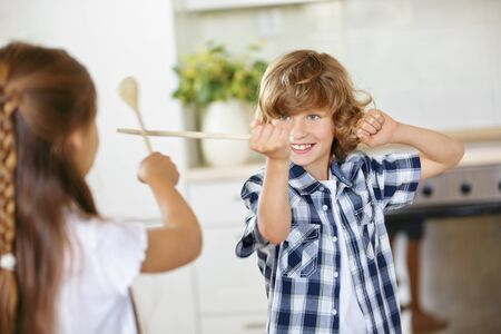 sibling rivalry: Boy and girl fighting in fun with wooden spoons in the kitchen