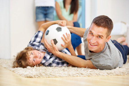 Father and son romping with soccer ball at home in the living room