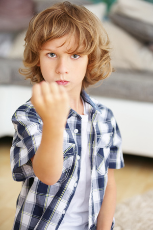 disobedience: Angry boy raising his fist at home Stock Photo