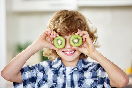 kiwi  fruit: Boy having fun with kiwi and holding the fruit in front of his eyes Stock Photo