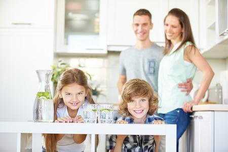 agua: Familia feliz y dos hijos en la cocina con agua de limón fresco Foto de archivo