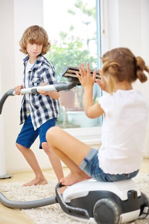 suck: Two kids playing with vacuum cleaner while cleaning at home