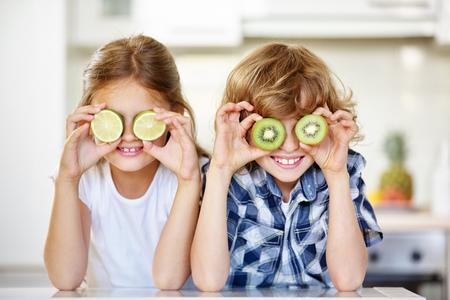 nonsense: Two kids in kitchen hiding their eyes behind fruits