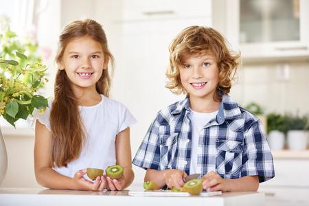 kiwi: Two happy kids cutting a kiwi in a kitchen