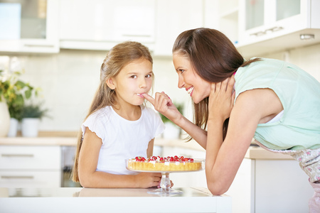 woman surprise: Mother and daughter tasting fresh fruitcake in the kitchen