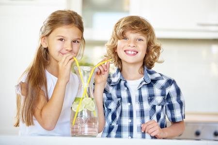 Niño y niña de beber agua de limón fresco con la paja en la cocina