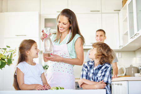 Mother and children with carafe water in the kitchen