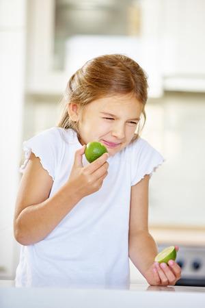 Meisje probeert te lime fruit te eten en het maken van een grimas Stockfoto