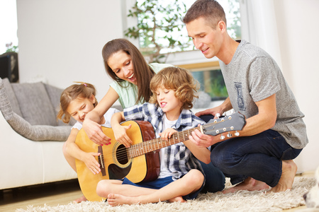 Parents and children playing guitar at home in the living room Foto de archivo