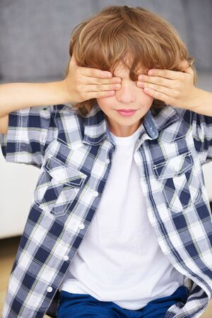 disobedience: Boy playing hide and seek and covering his eyes with his hands at home