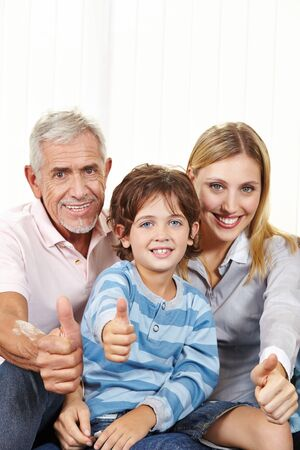 family  room: Happy family in living room holding thumbs up for congratulations