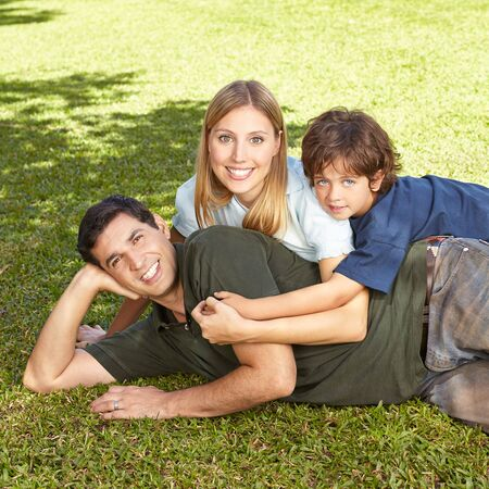 family together: Happy family with son laying in summer in grass of a garden