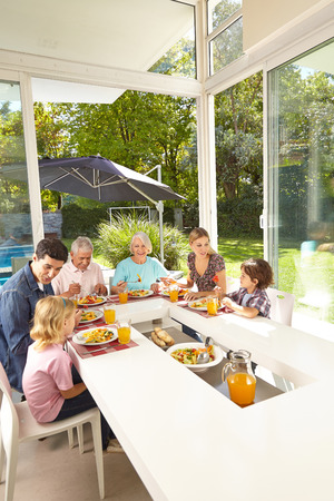sunroom: Family in three generations eating together at lunch table in summer