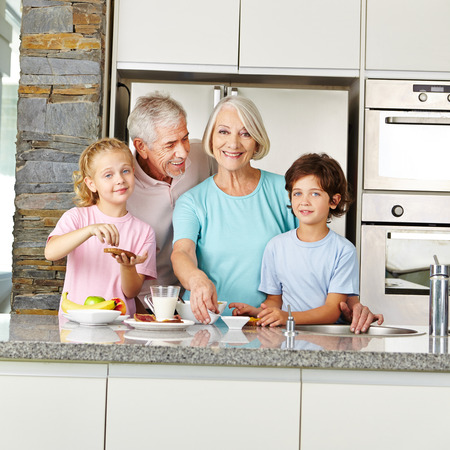 niños desayunando: Nietos con los abuelos felices en la cocina preparando el desayuno Foto de archivo