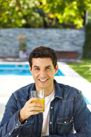 sunroom: Happy man drinking fresh orange juice in summer Stock Photo