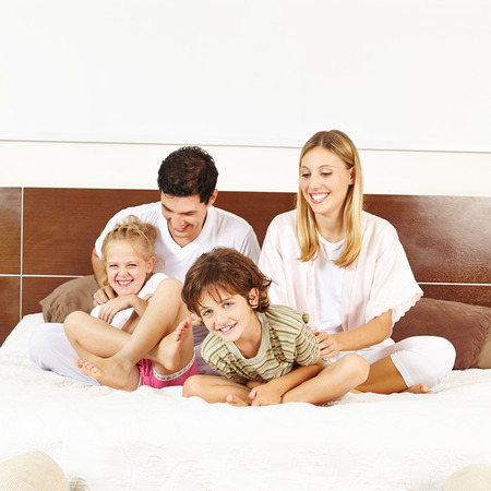 family tickle: Laughing family having fun with children on bed in a bedroom