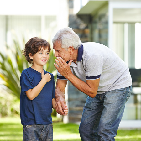 old people: Grandfather whispering a wish in the ear of his grandson in a garden Stock Photo