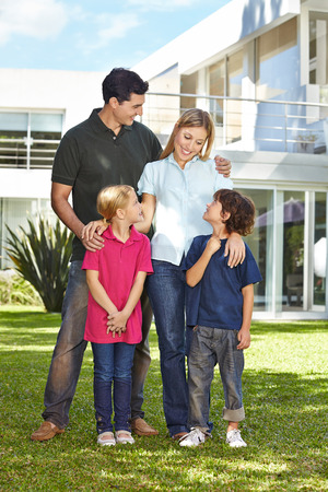 house family: Happy family with two children in front of a modern house