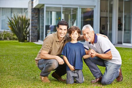 dad: Happy child with his father and grandfather in a garden in front of a house