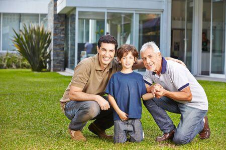 grandfather: Ni�o feliz con su padre y abuelo en un jard�n en el frente de una casa Foto de archivo