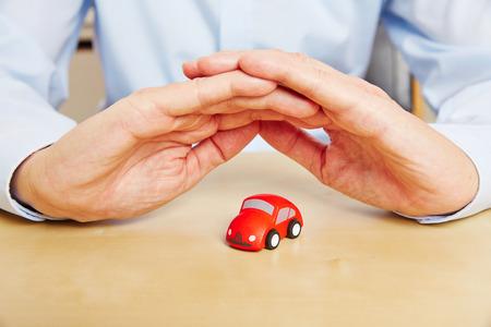 seguro: El seguro de coche con las manos sobre vehículo rojo como un símbolo Foto de archivo