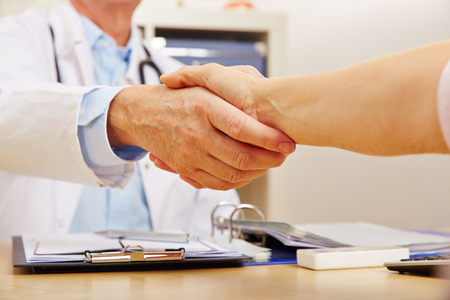 advice: Handshake with doctor and patient at the desk in the doctors office