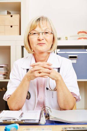 old desk: Old smiling female doctor sitting at desk in her office