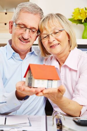 family budget: Happy senior couple holding a small house on their hands Stock Photo