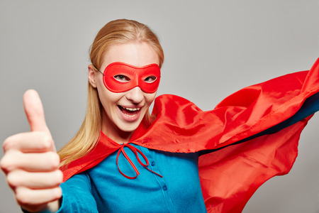 Smiling woman dressed up as a superhero holding her thumb up Stock Photo