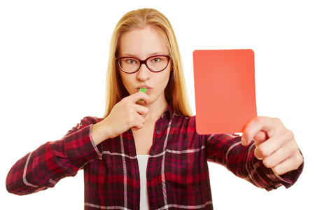 kicked out: Woman with whistle showing a red card after a foul Stock Photo