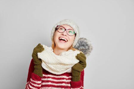 stocking cap: Smiling young woman wearing a scarf and a cap looking up